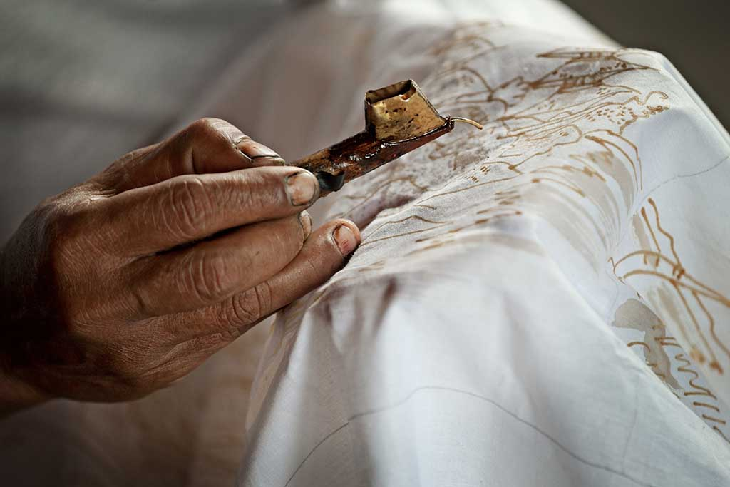 Close up of a Batik artist painting on a white cloth, Indonesia